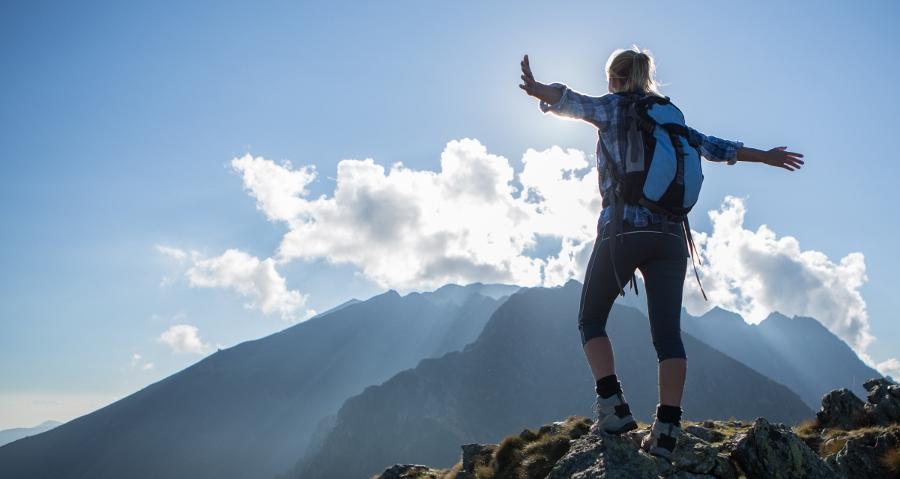 Success hiker at top of mountain peak