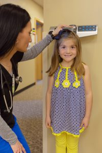 child getting height measured at doctor office