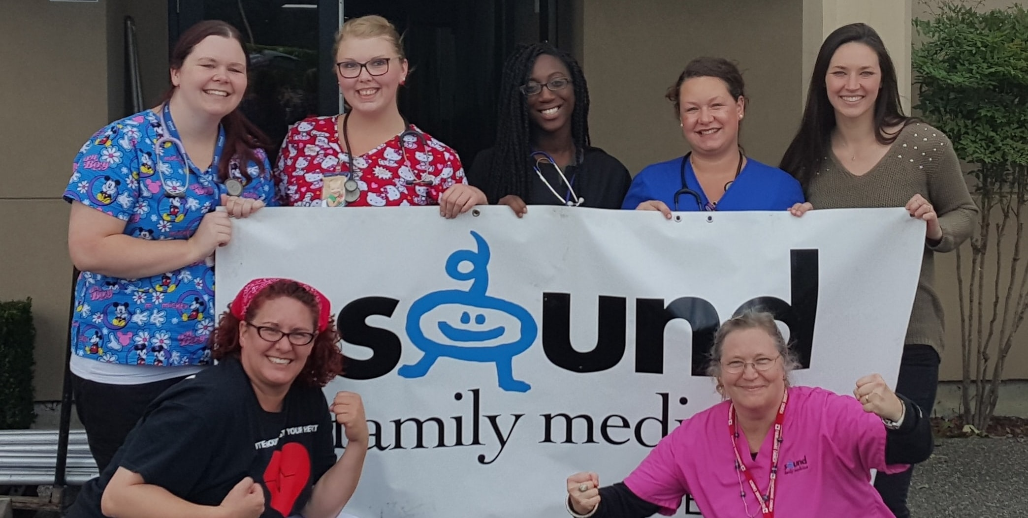 Sound Family Medicine staff holding banner at Puyallup community event