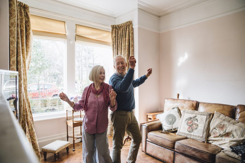 Senior couple are enjoying a dance in the living room of their home.