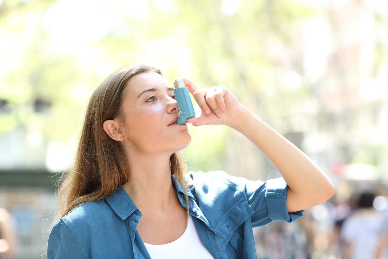 Asthmatic woman using inhaler